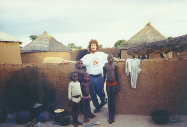 Bawku, Ghana, 1994. Peace Corps volunteer Wayne Breslyn stands with several Kusasi children in their village. On the left of the picture is the area where meals are prepared. Photo by Peace Corps Volunteer Wayne Breslyn.
